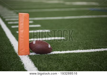Selective focus photo of the pylon and touchdown line on a football field. Low angle view from the end zone in an indoor stadium
