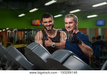 Happy smiling senior man on jogging machine and his personal trainer showing thumbs up gesture. Male adult working out with coach in gym. Healthy lifestyle, fitness and sports concept.