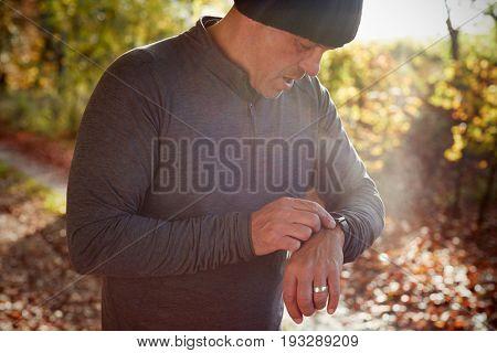 Mature Man On Autumn Run Checking Activity Tracker