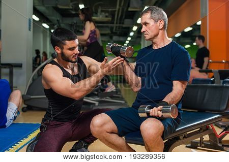 Senior man working out in gym with personal trainer. Young friendly fitness instructor Healthy lifestyle, fitness and sports concept.
