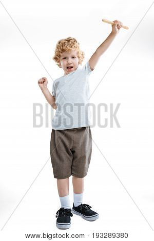 little kid boy showing gesture of success and holding wooden stick isolated on white