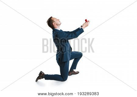 young man in suit standing on one knee and making marriage proposal isolated on white