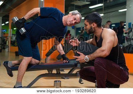 Senior caucasian man doing weight exercise with personal trainer. Male adult exercising with assistance of fitness instructor. Healthy lifestyle, fitness and sports concept.