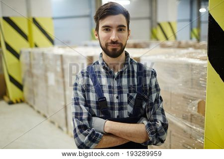 Young storehouse worker looking at camera