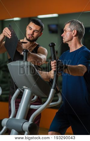 Senior man working out in gym with assistance of personal trainer. Fitness coach showing training plan on clipboard. Healthy lifestyle, fitness and sports concept.