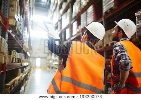 Revision managers discussing amount of loaded goods in racks