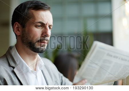 Serious man concentrating on reading article from newspapaper