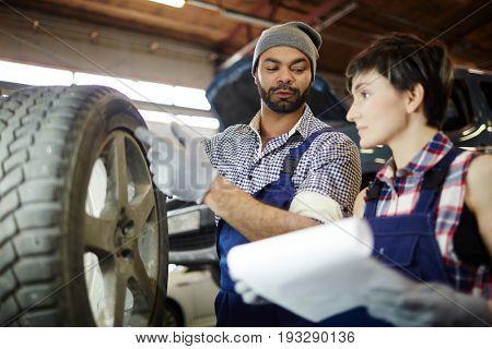 Repairman showing car tyre to his apprentice