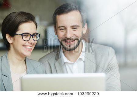 Happy economists reading online data in laptop