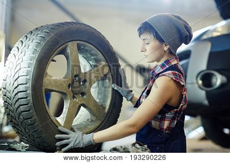 Repair service worker going to change tire of car