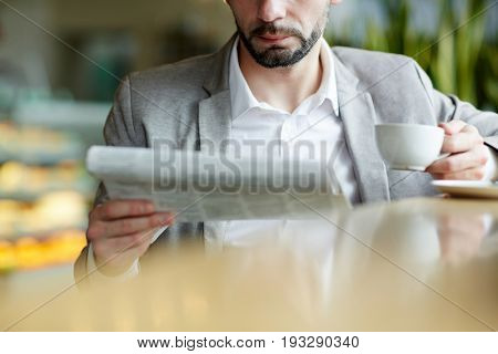 Newspaper and cup of tea held by serious businsessman