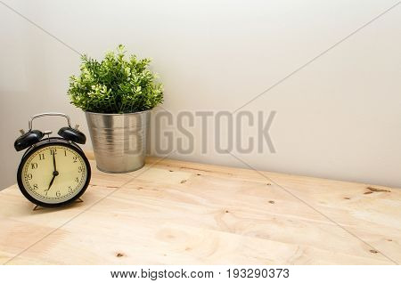black vintage alarm clock times at 7 o'clock morning and green tree in silver pot small decorative on wooden table and white wall vintage tone retro style