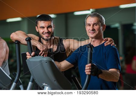 Happy smiling senior man on jogging machine and his personal trainer in gym. Male adult working out with coach. Healthy lifestyle, fitness and sports concept.