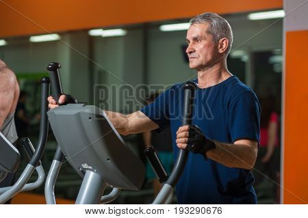 Senior man exercising on elliptical machine in gym. Healthy lifestyle, fitness and sports concept.