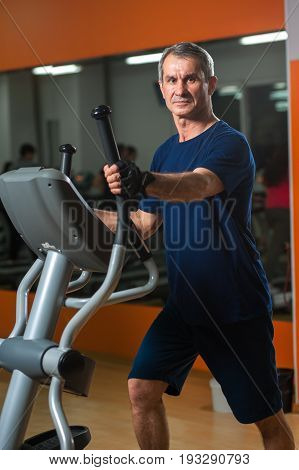 Cheerful senior man working in gym. Male adult exercising on elliptical machine. Healthy lifestyle, fitness and sports concept.