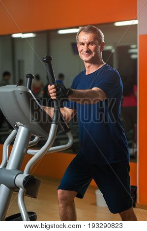 Happy smiling senior man working in gym. Male adult exercising on elliptical machine. Healthy lifestyle, fitness and sports concept.