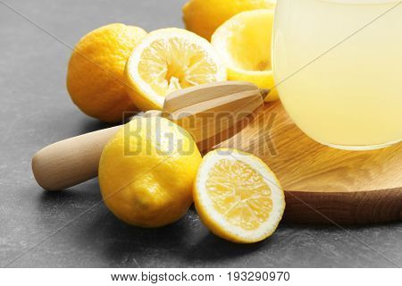 Squeezer and lemons on dark background
