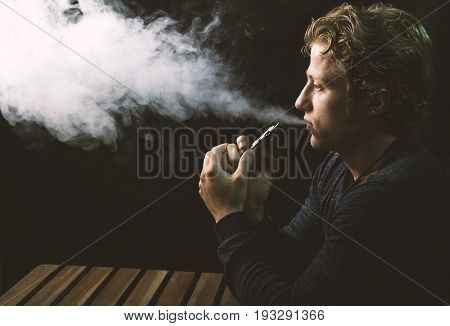 Isolated Caucasian White Man Holding And Vaping An Electronic Cigarette.