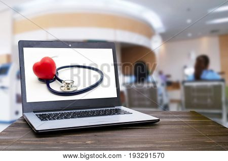 Laptop computer with red heart and stethoscope on white screen on wooden table with blurred view of patient sitting wheelchair in hospital background heart health care and medical technology concept