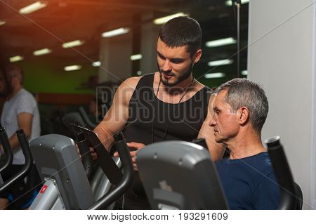 Senior man working with personal trainer in gym. Male adult exercising on machine with assistance of fitness coach. Healthy lifestyle, fitness and sports concept.