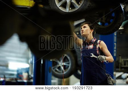 Female technician with wrench repairing car