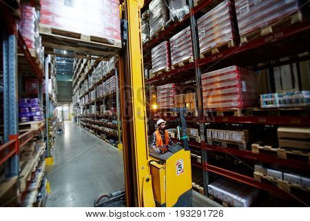 Worker on forklifter loading packed goods for wholesale