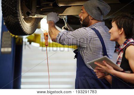 Two car technicians working in garage
