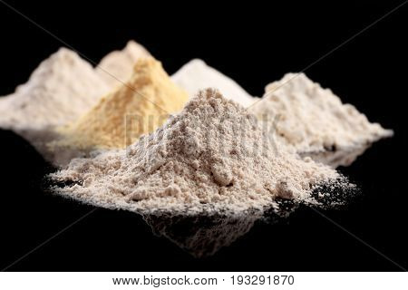 Different types of flour on black background
