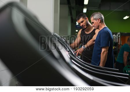 Senior man exercising on jogging machine. Personal trainer working with elderly man client. Healthy lifestyle, fitness and sports concept.