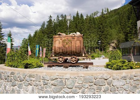 Bad Gastein Austria - JUNE 08 2017: Old mining truck in front of the Health resort Heilstollen a former mining tunnel. Near Bad Gastein Austria Europe. Hammer and pick as symbols of mining.