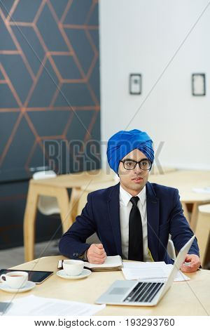 Businessman or tv newscaster in turban sitting by workplace