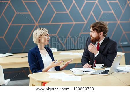 Confident young female voicing her ideas while talking to colleague