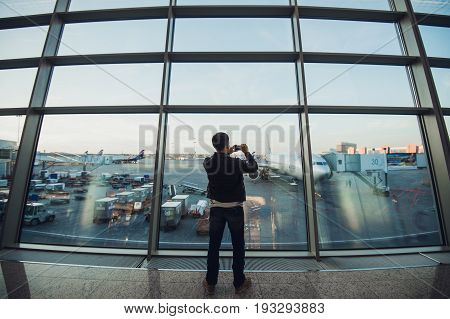 Handsome man standing beside glass wall in modern airport terminal, taking photo picture of airplane aircraft, travelling to other countires