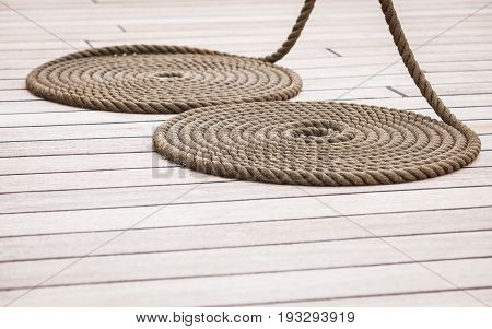 Old nautical objects concept. Circle rounded antique chest rope coil on wooden floor.