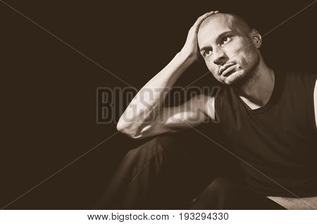 Depression. Depressed man sitting in the dark with emptiness in his eyes. Dark image. Dark background.