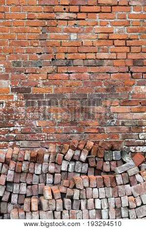 Old distressed red brick wall background with a pile of bricks in the foreground