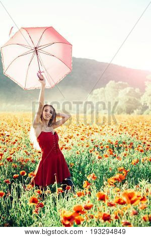 pretty happy girl with long curly hair in red dress hold pink umbrella in field of poppy seed flower on green stem on natural background summer drug and love intoxication opium
