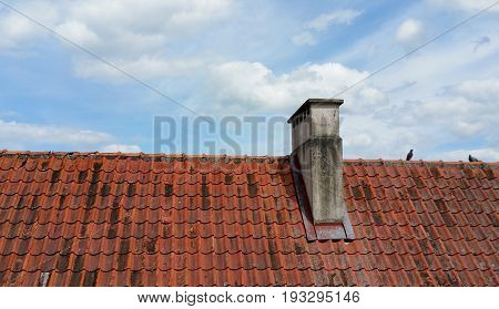 Roof tiles and blue sky with clouds