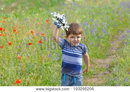 Happy boy play with airplane toy on meadow full of flowers. Little boy dreams to be a pilot one day and play with airplane