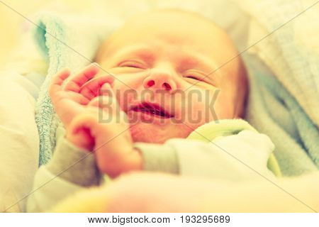Infant care beauty of childhood concept. Little newborn baby sleeping calmly in bed surrounded with blankets making funny faces.