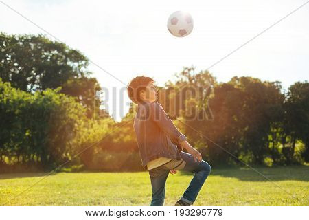 Fly high. Good looking persistent excited kid mastering his game skills while enjoying warm weather and spending the day outdoors