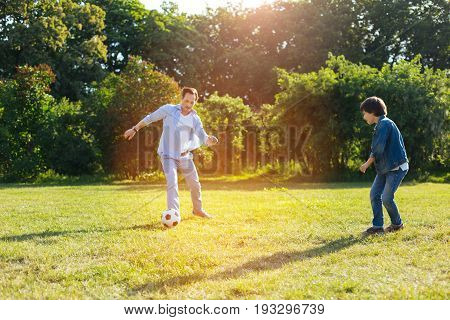 Boy playing. Handsome energetic creative father and his child taking the chance and while enjoying an active lifestyle spending some time outside the city