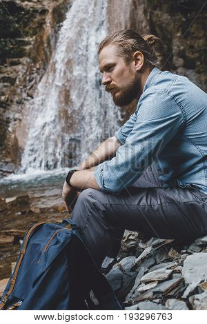 Male Tourist Sitting On The Rocks Near Waterfall Side View. Hiking Destination Experience Lifestyle Concept