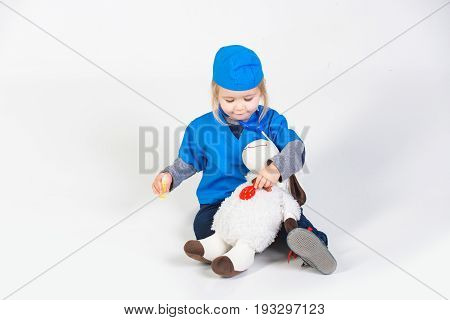 Small Boy In Doctor Uniform Playing Vet With Toy Animal