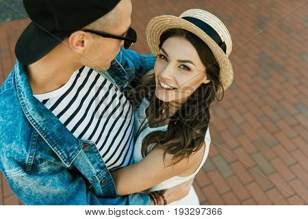 Happy Stylish Girlfriend In Straw Boater And Her Boyfriend Hugging On The Street