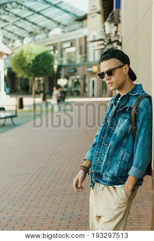 Stylish Young Man In Denim Jacket And Sunglasses Standing Outdoor Looking Away