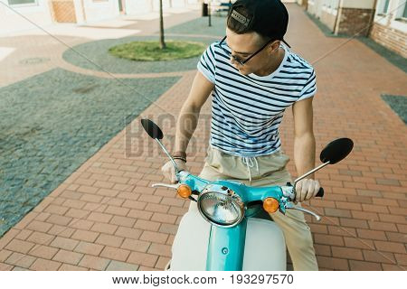 Stylish Young Man In Cap And Sunglasses Riding Moped And Looking Down