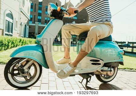 partial view of man sitting on retro scooter parked on street
