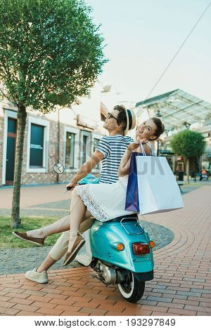 Young Casual Couple Riding On Moped And Holding Shopping Bags Outdoors