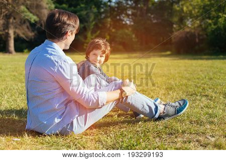 Mens conversation. Charming cheerful wonderful kid and his dad sitting on green grass and enjoying warmth and sunlight while having a lovely conversation